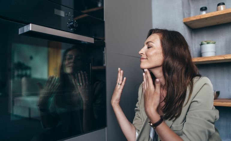 woman smelling oven